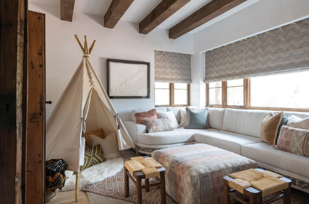 """Nicknamed the """"Saint's Room"""" by its Santa Fe homeowners, this vibrant guest bedroom features a painted sun (in Sherwin-Williams Brittlebush) and several authentic retablos. The bed is covered in textiles from Isabelle de Borchgrave's Fabricut collection. Photo: Michael Hunter"""